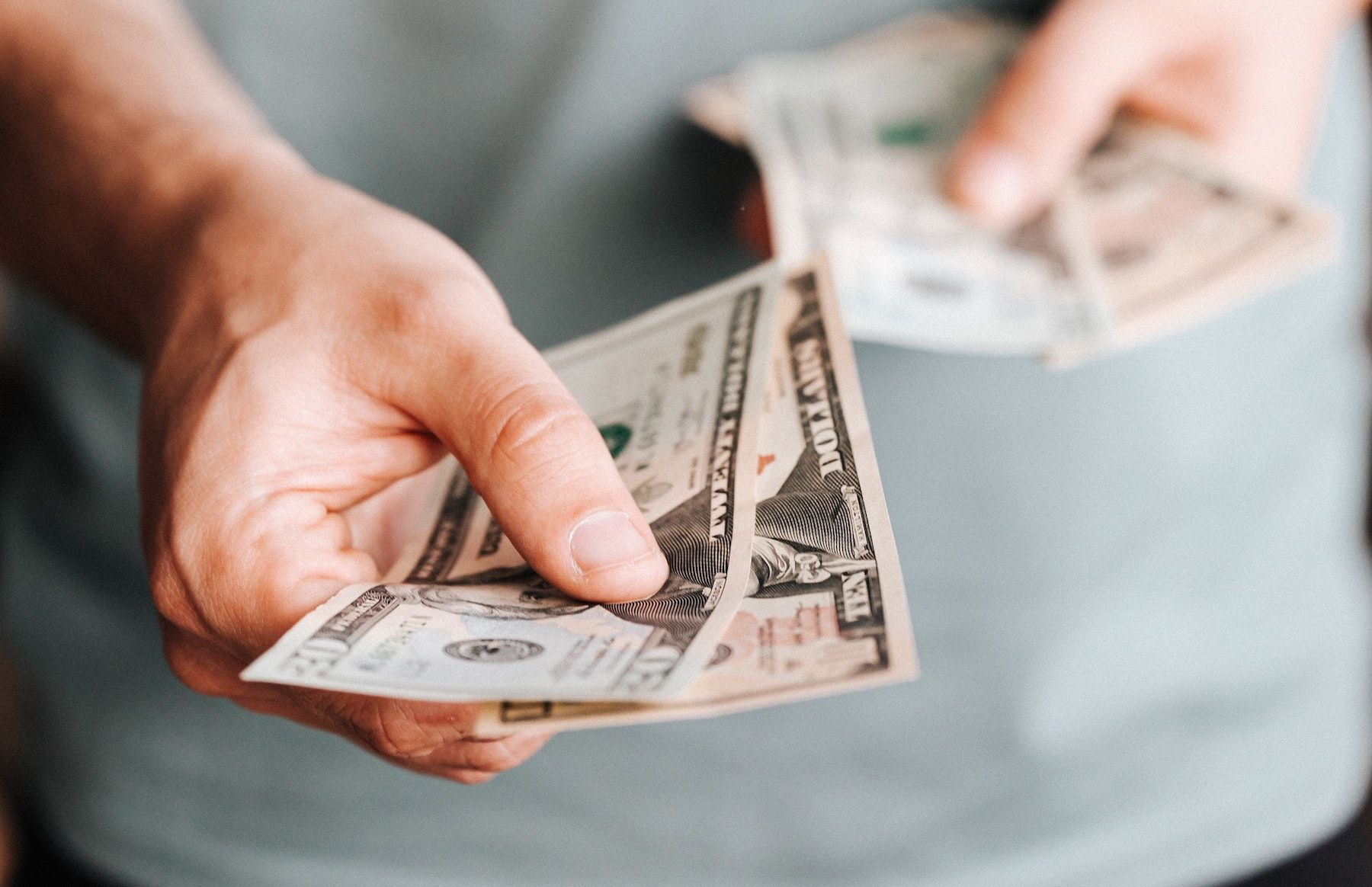 A person holding several twenty and 10 dollar bills in their hand.