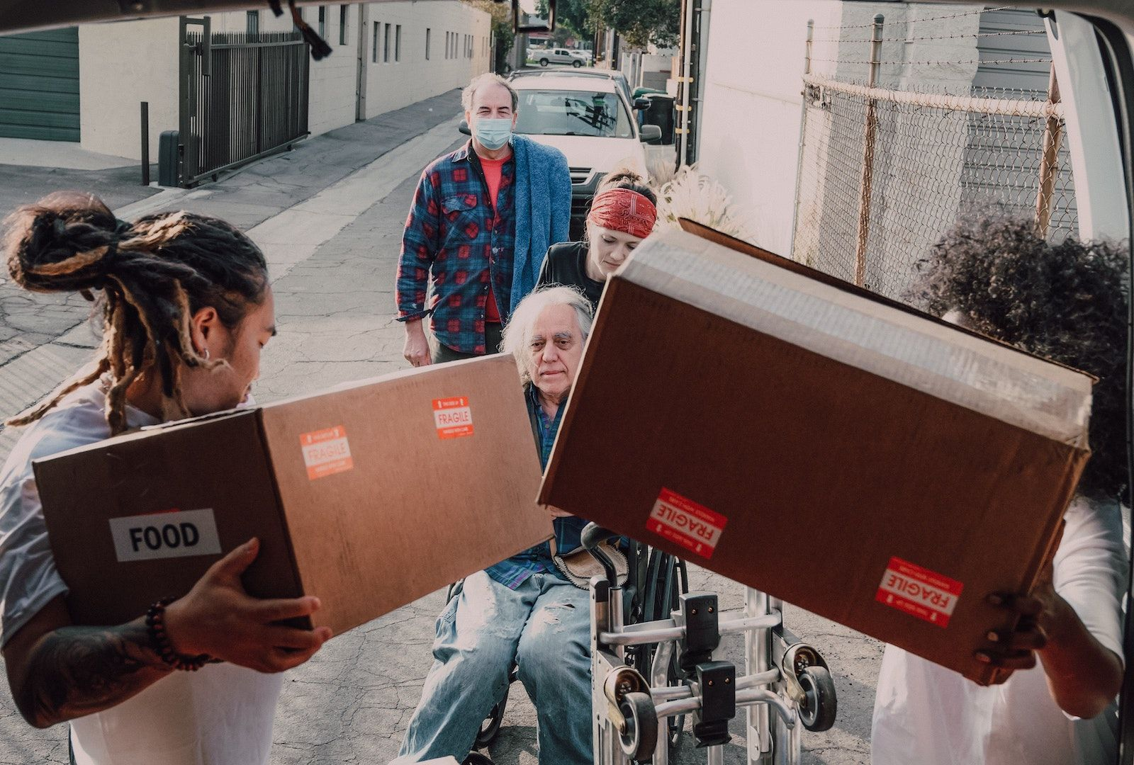 A group of volunteers unloading and handing boxes of food to an elderly individual in aa wheelchair.